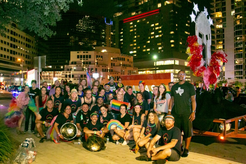 Kasasa employees participate in the 2018 Austin Pride Parade. The company logo can be seen in the top right corner.