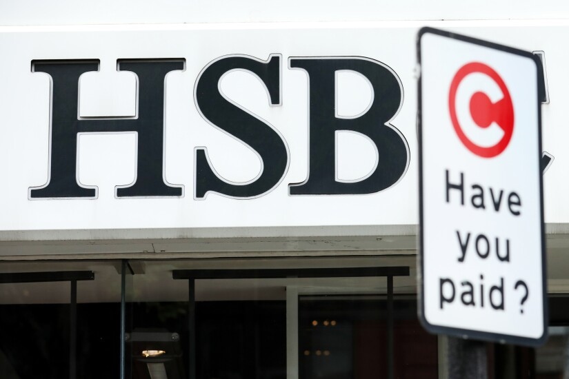 A sign for the London Congestion Charge stands outside a HSBC bank branch in London.