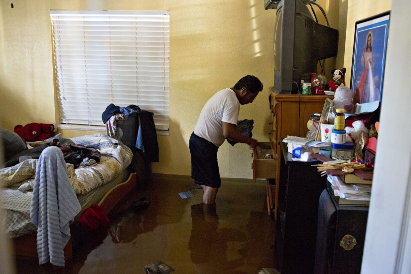 A resident collects personal belongings from his flooded home in Bonita Springs, Florida, U.S., on Tuesday, Sept. 12, 2017.