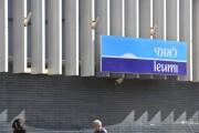 Pedestrians walk under Bank of Leumi sign