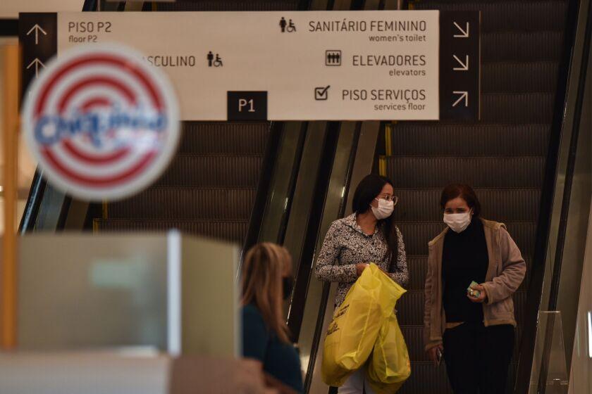 Shoppers wearing protective masks take an escalator in the Patio Brasil shopping mall in Brasilia, Brazil.