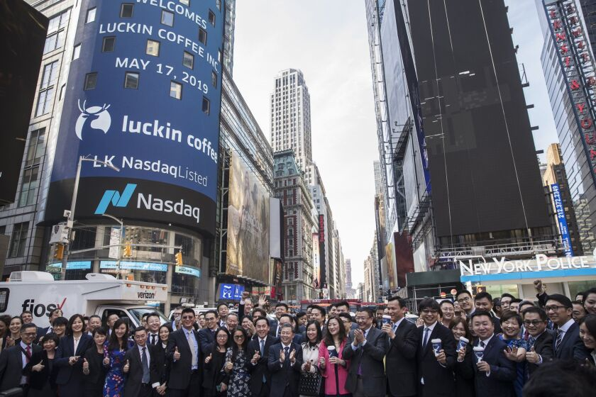 Jenny Qian Zhiya, chief executive officer of Luckin Coffee Inc., center, and Charles Zhengyao Lu, chairman and founder of Luckin Coffee Inc., center right, stand for photographs with employees in Times Square after ringing the opening bell during the company's initial public offering (IPO) at the Nasdaq MarketSite in New York, on Friday, May 17, 2019.
