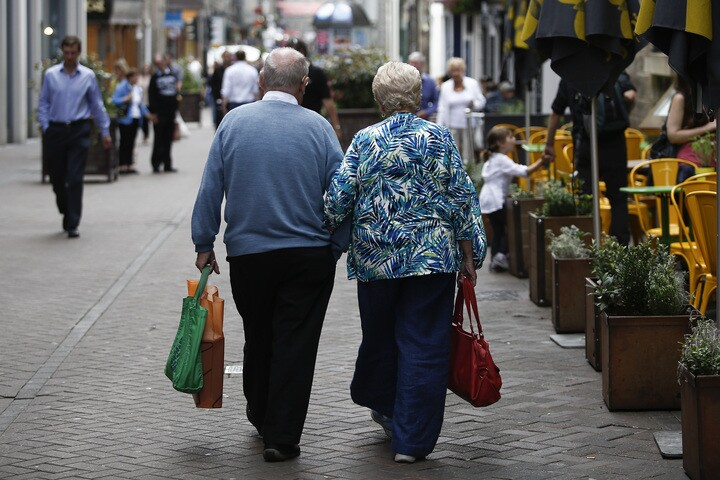 An elderly couple walk arm-in-arm past an outdoor cafe terrace in Edinburgh, U.K., on Wednesday, July 31, 2013. The latest opinion polls show supporters of Scottish First Minister Alex Salmond's campaign for independence lagging behind those in favor of the status quo by more than 20 percentage points ahead of the Sept.18, 2014, referendum. Photographer: Simon Dawson/Bloomberg