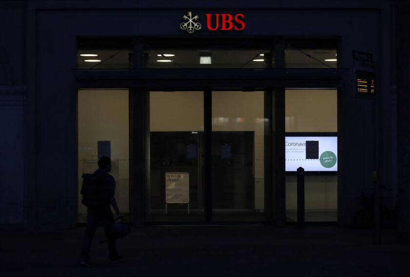 An illuminated logo sits on display above the entrance to a UBS Group AG bank branch at night in Bern, Switzerland, on Sunday, April 19, 2020. A UBS appeal of a record 4.5 billion-euro ($4.9 billion) French fine for helping clients stash undeclared funds in offshore accounts was postponed over concerns related to coronavirus pandemic, according to people familiar with the case.Photographer: Stefan Wermuth/Bloomberg