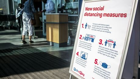 A sign advising of social distancing measures in place stands on display at the entrance to a Pick n Pay Stores Ltd. supermarket in Johannesburg, South Africa, on Monday, May 11, 2020.