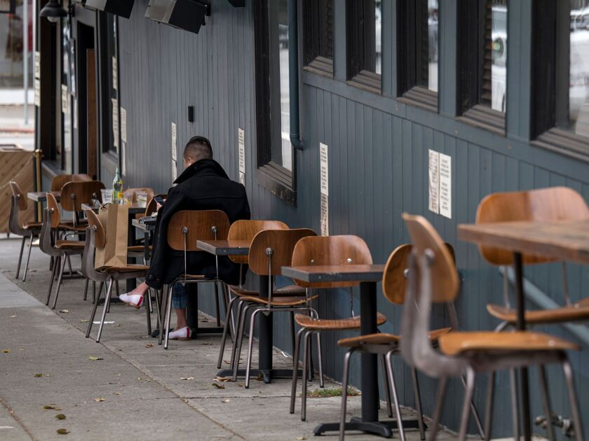 A person sits at a table outside of a restaurant in San Francisco, on Aug. 5.