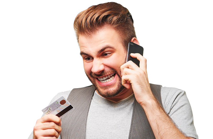 Stock image of a man angry on the phone with ATM card in hand