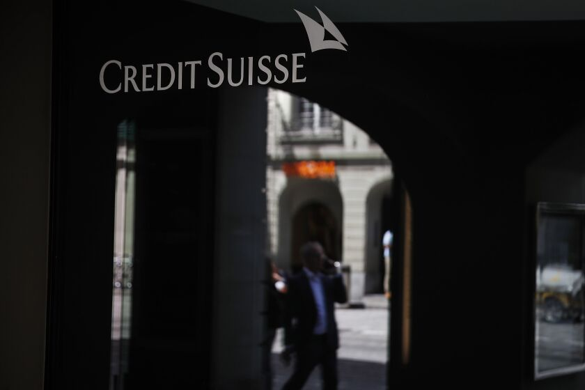 A sign hangs above the entrance to a Credit Suisse Group AG bank branch in Bern, Switzerland, on Thursday, June 18, 2020. The Swiss economy is expected to suffer its biggest contraction since the mid-1970s this year, with financial stability risks increasing globally due spiraling corporate and state debt. Photographer: Stefan Wermuth/Bloomberg