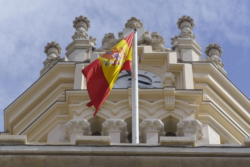 A Spanish national flag flies from the roof of the Spanish central bank in Madrid.