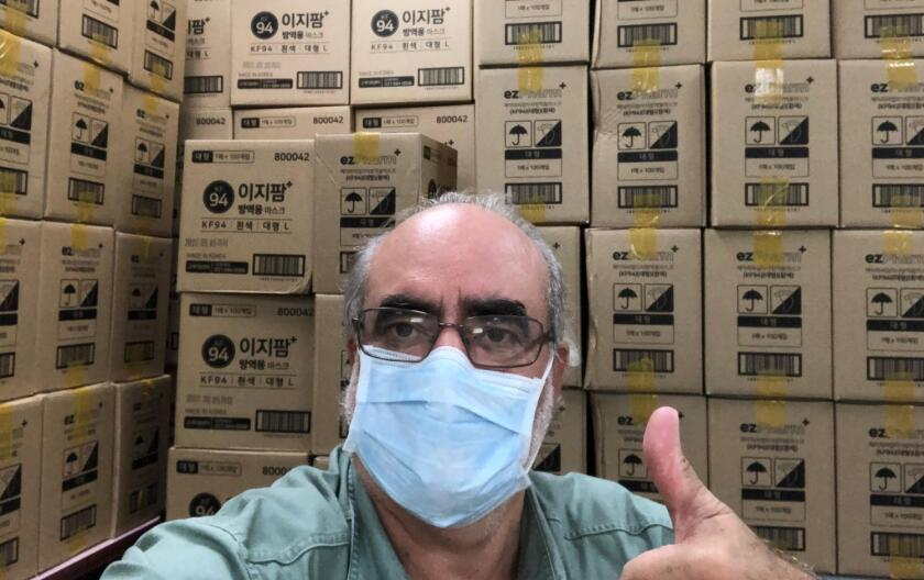 Brian Branch, president and CEO of the World Council of Credit Unions, poses in front of boxes of face masks donated by the Credit Union Federation of Korea. WOCCU will help distribute them to CUs around the world.