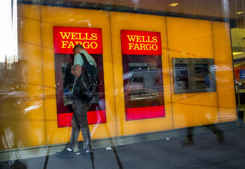 A man uses a Wells Fargo ATM inside a branch in New York.