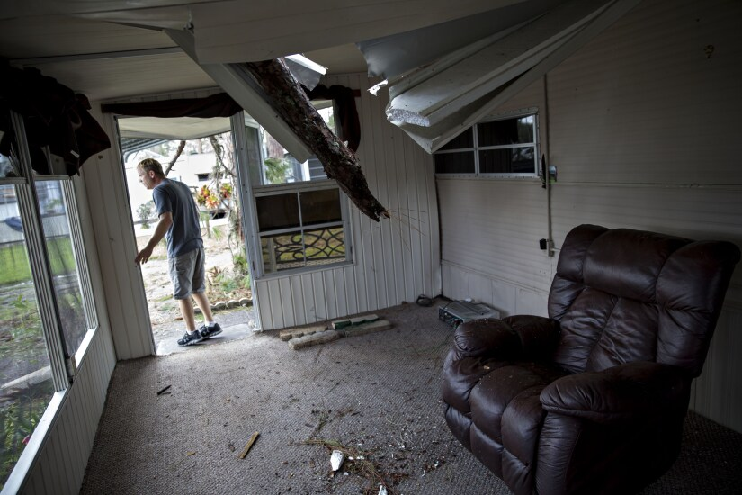 A resident surveys the damage to his trailer after a tree punctured the roof at the Camp Inn RV Park in Frostproof, Florida, during Hurricane Irma.