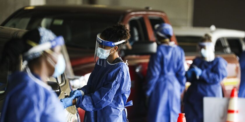 Healthcare workers test people at a COVID-19 testing site in the parking garage for the Mahaffey Theater in St. Petersburg, Florida.