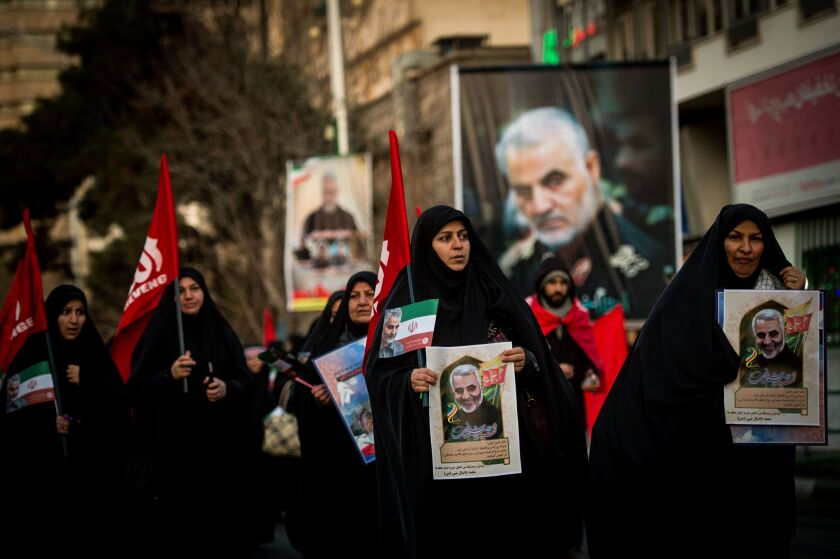 Mourners carry images of Iranian General Qassem Soleimani during the funeral ceremony in Tehran, Iran, on Monday.