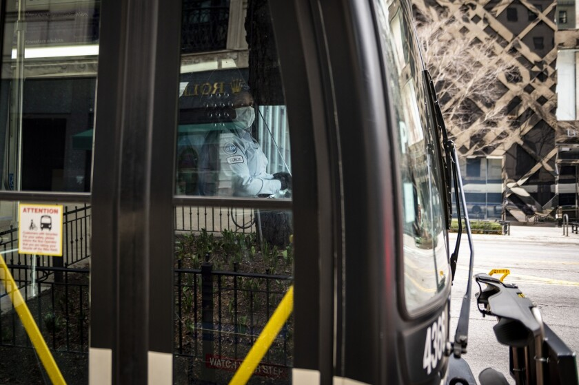 A Chicago Transit Authority (CTA) bus driver wears a protective mask