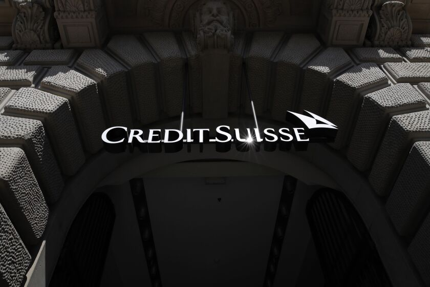 A logo hangs above the entrance to the Credit Suisse Group AG headquarters in Zurich, Switzerland, on Friday, April 17, 2020. Credit Suisse compensated managers and employees with additional shares in the bank after the price dropped sharply during the depths of a market correction spurred by the coronavirus outbreak. Photographer: Stefan Wermuth/Bloomberg