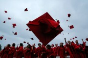 Students throw their mortar boards into the air in celebration during graduation.