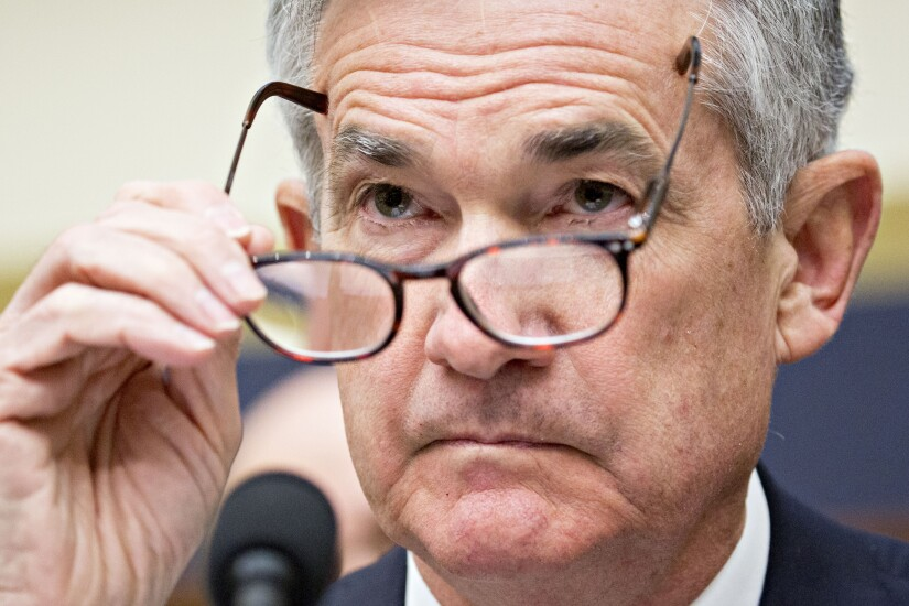 Jerome Powell, chairman of the Federal Reserve, puts on his glasses during a House Financial Services Committee hearing in Washington.
