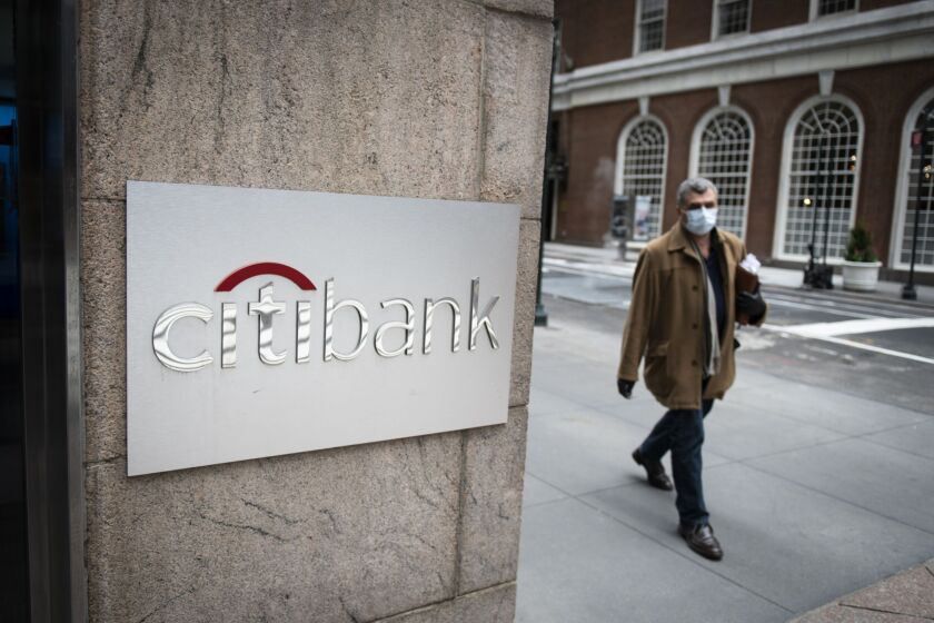 A pedestrian wearing a protective mask walks past a Citibank branch in New York on April 10, 2020.