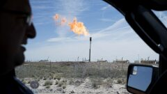 A gas flare is seen through the window as a Royal Dutch Shell Plc representative drives near Mentone, Texas.