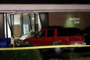 A red SUV is seen parked outside the damaged SunTrust bank early Thursday, Jan. 24, 2019, in Sebring, Fla. Authorities say five customers were shot and killed at the bank on Wednesday.