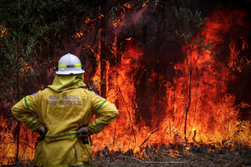 A New South Wales (NSW) Rural Fire Service volunteer watches a fire in bushland during back-burning operations in bushland near the town of Kulnura, New South Wales, Australia, on Thursday, Dec. 12, 2019.