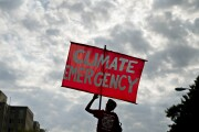 """A protester holds a sign that reads """"Climate Emergency"""" while blocking an intersection during the Shut Down DC climate demonstration in Washington Sept. 23, 2019."""