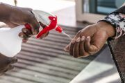 A worker sprays sanitizer into the hands of a shopper at a supermarket in Johannesburg, South Africa in May.