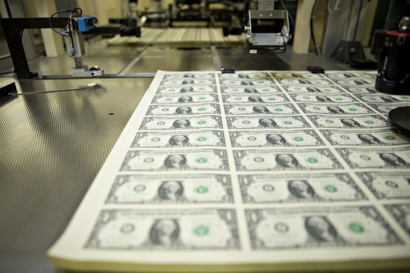 Stacks of 2017 50 subject uncut sheets of $1 dollar notes bearing the name of U.S. Treasury Secretary Steven Mnuchin sit in a machine at the U.S. Bureau of Engraving and Printing in Washington, D.C., U.S., on Wednesday, Nov. 15, 2017.