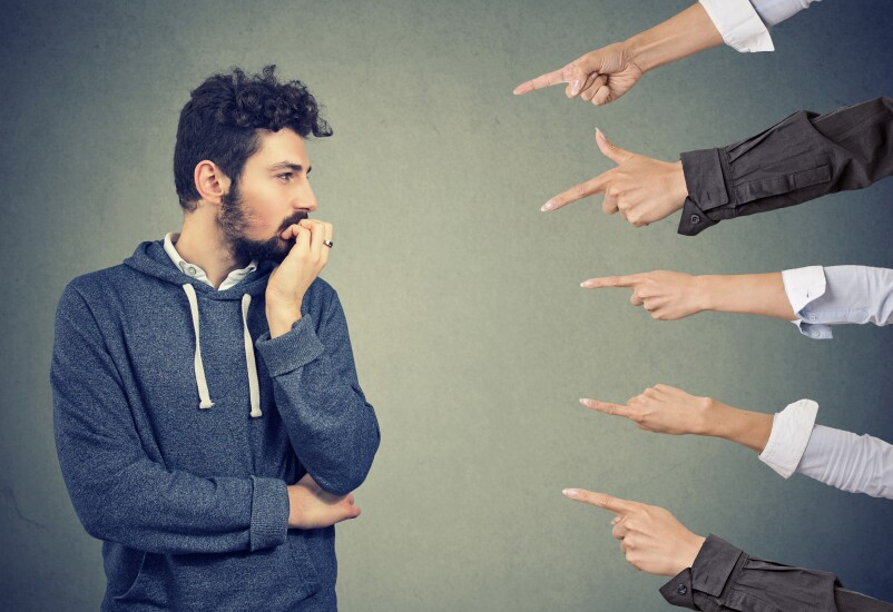 Anxious man judged by different people. Concept of accusation of guilty guy. Negative emotions face expression feeling