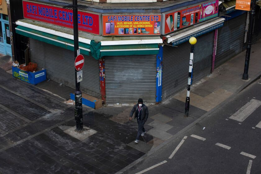 A man in a protective face mask walks past a shuttered store in the Brixton district of London on April 4, 2020