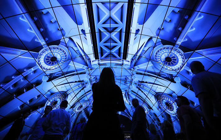 Conference goers walk under a electronic display