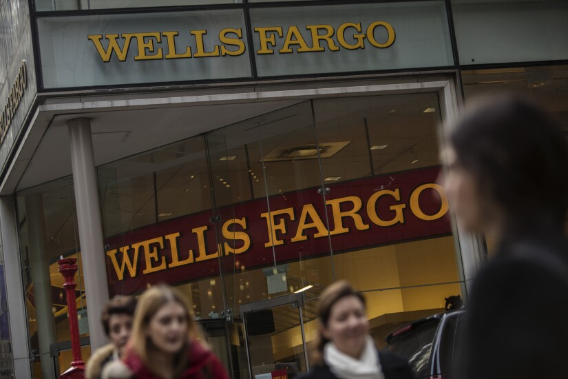 Pedestrians pass in front of a Wells Fargo branch in New York.