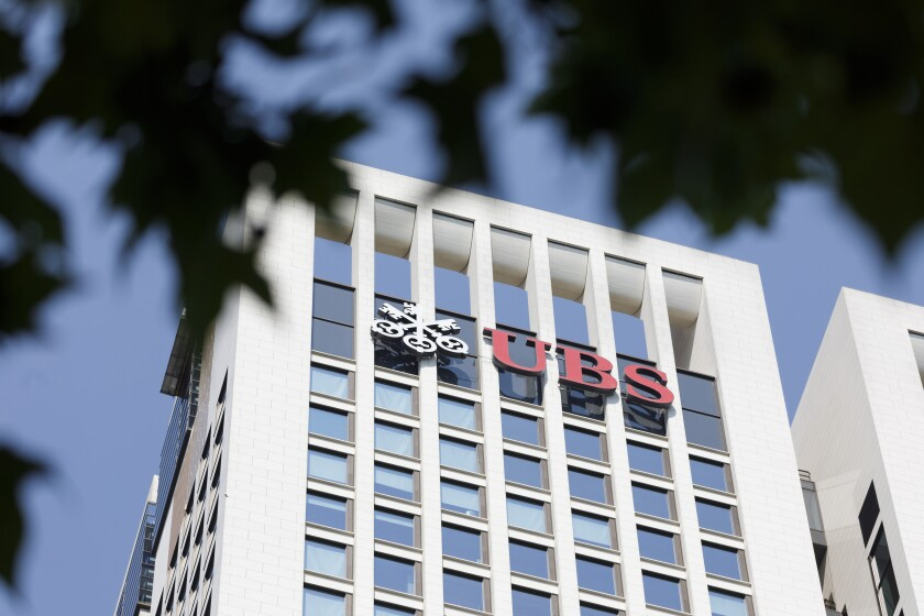 The UBS Group AG logo sits on the bank's skyscraper offices in Frankfurt, Germany, on Tuesday, July 17, 2018. Frankfurt's efforts to attract bankers escaping Brexit are in danger of losing momentum. Photographer: Alex Kraus/Bloomberg