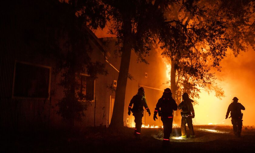 Firefighters use flashlights to search the perimeter of a building at the Soda Rock Vineyards during the Kincade fire in Healdsburg, California, U.S., on Sunday, Oct. 27, 2019. The wildfire that erupted in Californias wine country minutes after a PG&E Corp. power line went down has prompted an expanded evacuation order, as officials warn high winds could drive the blaze toward one of the regions largest towns. Photographer: Phil Pacheco/Bloomberg