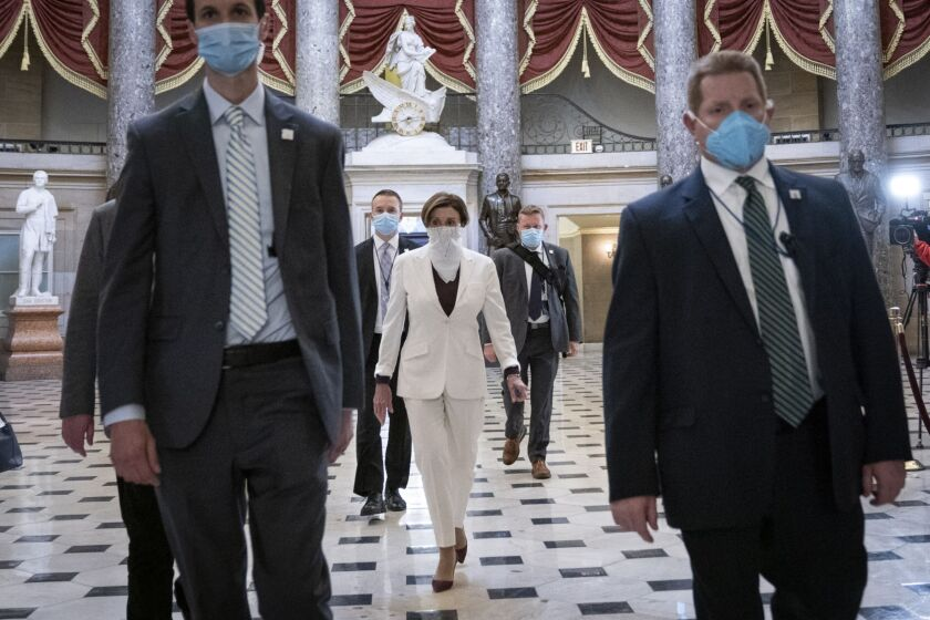 Lawmakers enter the House chamber wearing protective masks.