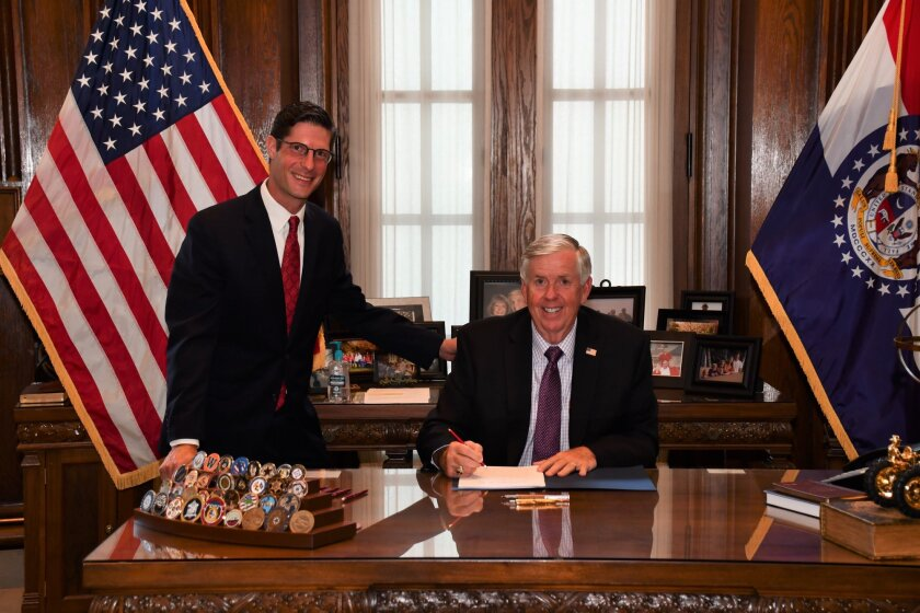 Missouri Gov. Mike Parson, right, signs into law a bill to modernize the Missouri Credit Union Act during a private bill-signing ceremony. He is pictured with Rep. Jack Bondon, one of the bill's cosponsors.