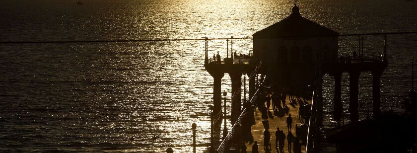 People walk on the pier at sunset in Manhattan Beach, California.