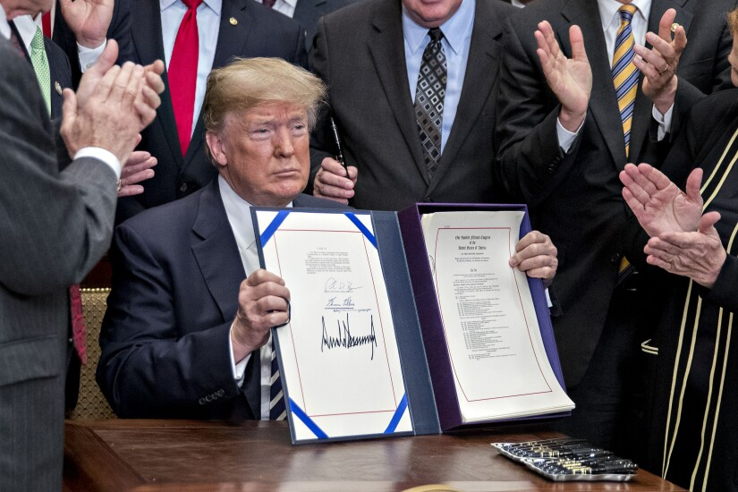 President Donald Trump holds up S. 2155, the Economic Growth, Regulatory Relief, And Consumer Protection Act, after being signed with administration officials and members of Congress in the Roosevelt Room of the White House.