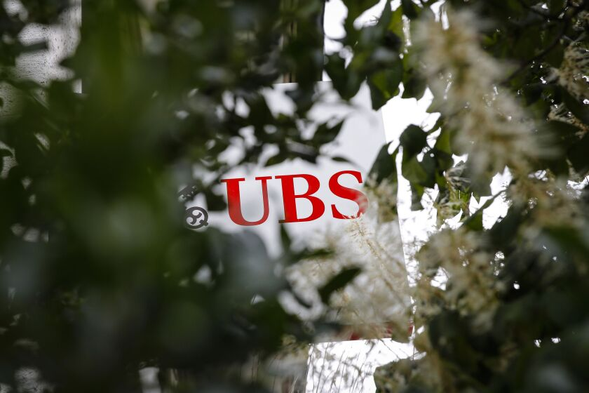 A sign sits on display outside a UBS Group AG bank branch in Worb, Switzerland, on Wednesday, July 15, 2020. U.S. President Donald Trump's trade war with China is spurring UBS's $2.2 billion multi-strategy hedge fund to make its biggest push yet into the Asian nation. Photographer: Stefan Wermuth/Bloomberg