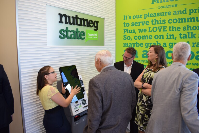 A Nutmeg State Financial Credit Union representative shows off kiosks in the self-service branch where consumers can do their banking and utilize select DMV services.
