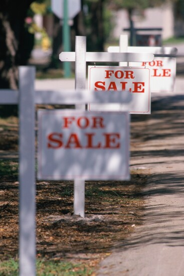 "Row of ""For Sale"" signs outside houses on a street."