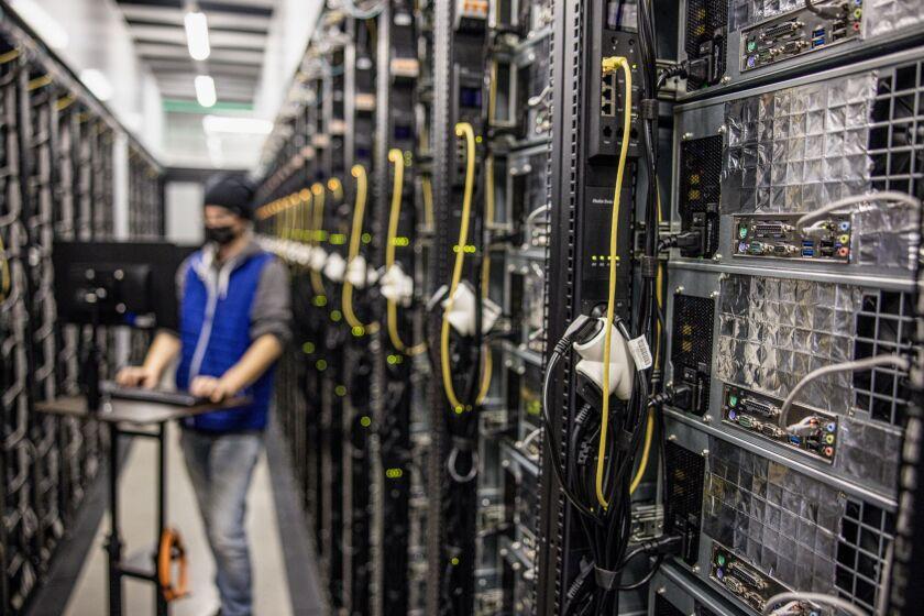 An engineer runs diagnostics on mining rigs at the Evobits crypto farm in Cluj-Napoca, Romania, on Jan. 22, 2021.