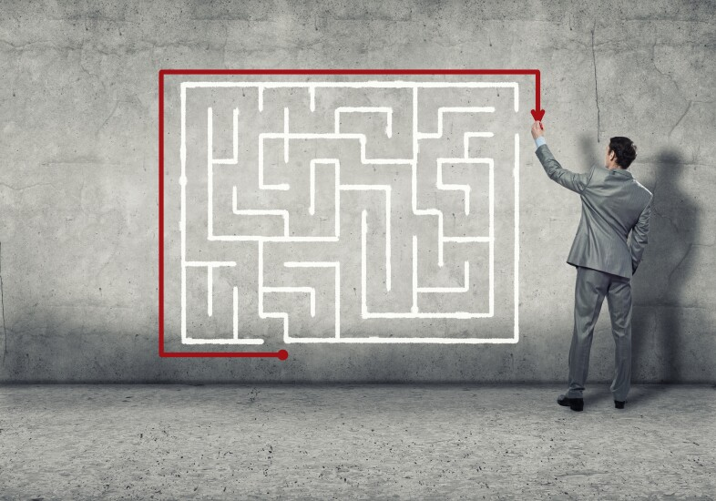 Businessman showing a route around maze instead of through it.