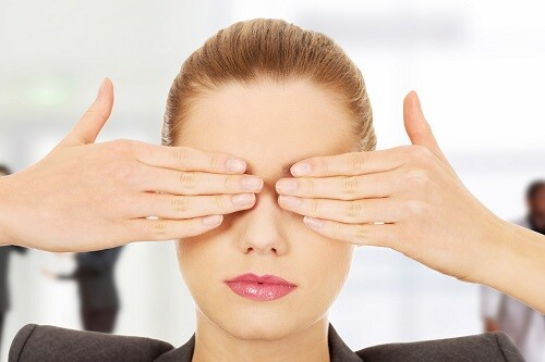 Young businesswoman covering eyes with hands.