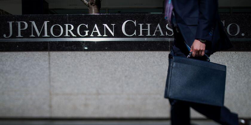A pedestrian walks by a JPMorgan Chase sign.