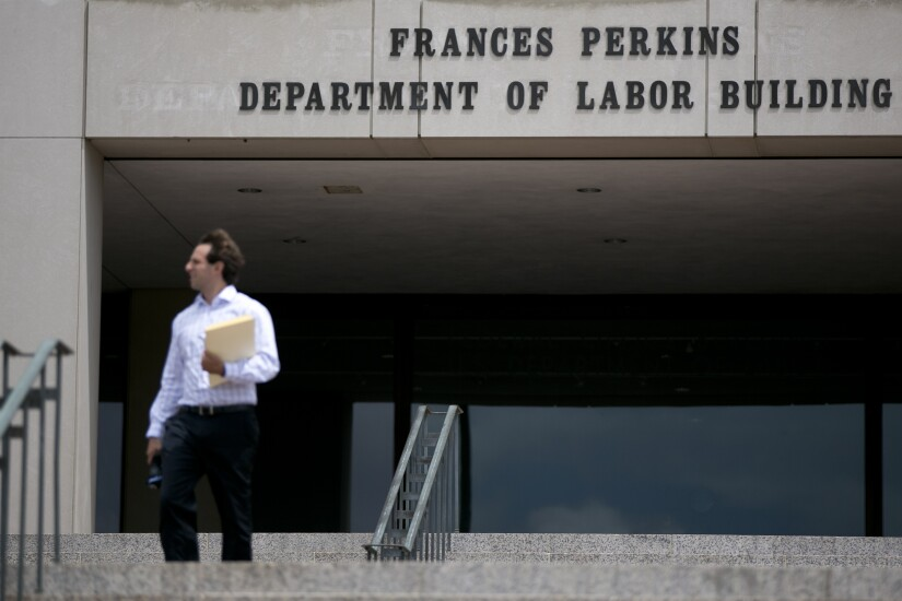 Department of Labor. man walks in front of building by Bloomberg News