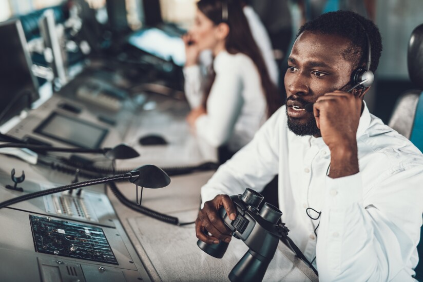 Center of dispatching maintenance. Waist up portrait of afro-american specialist speaking on headset microphone while working on navigation controller board