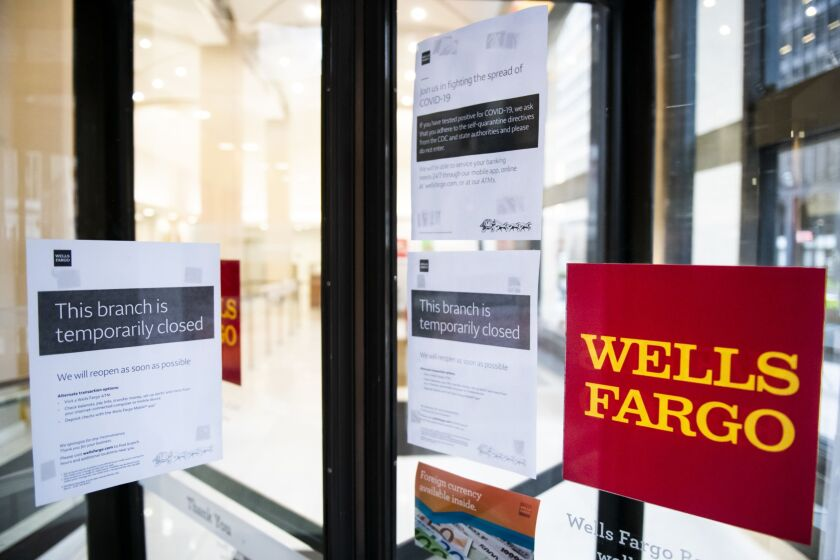 Temporarily closed sign is displayed in the window of a Wells Fargo branch in an effort to stem the spread of COVID-19 in New York April 2020