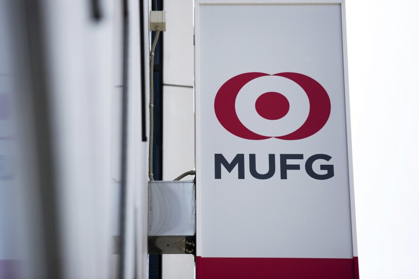 The logo of Mitsubishi UFJ Financial Group (MUFG) is displayed on a sign outside a Bank of Tokyo-Mitsubishi branch in Tokyo.